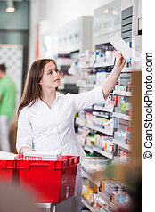 Female at drugstore - Female pharmacist keeping medicine box...