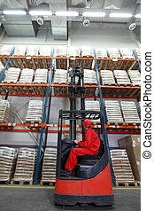 worker lifting sacks with forklift - Worker in red uniform...