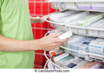 Man Holding Medication Box - Cropped image of man holding...