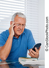 Senior Man Holding Calculator - Serious senior man looking...