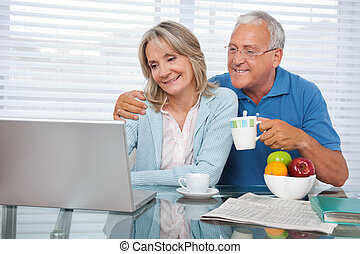 Happy Couple Using Laptop - Happy couple using laptop while...