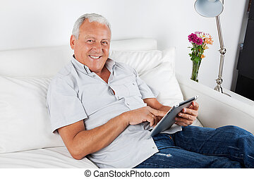 Senior Man Using Digital Tablet PC - Portrait of smiling...