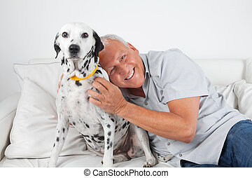 Senior Man Sitting With His Pet Dog - Portrait of senior man...