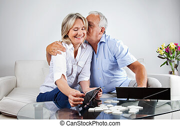 Elderly Couple Playing Games - Loving husband kissing his...