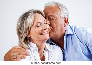 Husband Kissing Wife on Cheek - Senior man giving his wife...