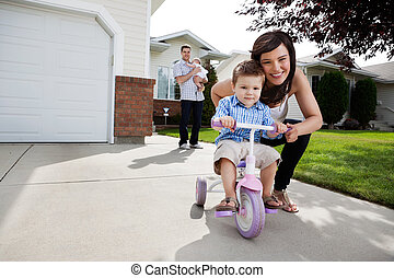 Loving Mother Teaching Son To Ride Tricycle - Portrait of...