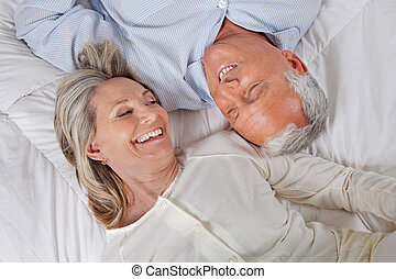 Couple Lying in Bed - Top view of happy couple lying in bed