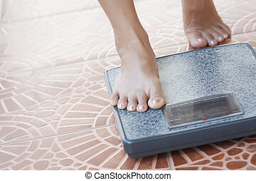 Female feet standing on the weight scale