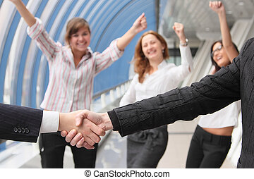 Hand shake of two businessmen against happy colleagues