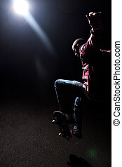Skateboarder Jumping Under Dramatic Lighting - A...