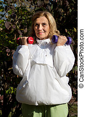elderly woman and dumb bells - old woman with dumb bells at...