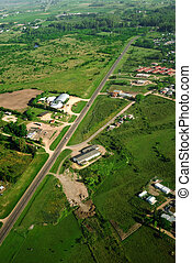 Green field and country road aerial view