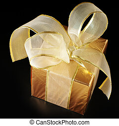 Gold foil gift with golden bow on black background.