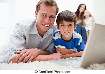 Boy with his father using laptop on the carpet - Boy with...