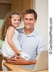Father showing laptop to his daughter