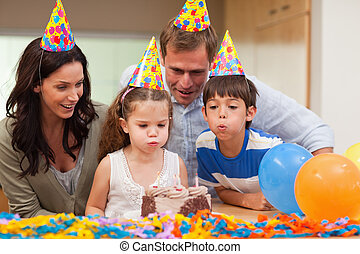 Young boy helping his little sister to blow out the candles...