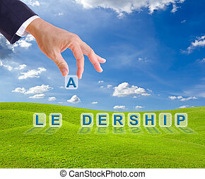 business man hand and leadership word on green grass meadow