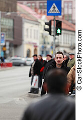 Man in the crowd - Image of a young businessman crossing a...
