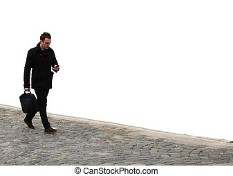 Businessman walking on a cobbled street in front of a white...
