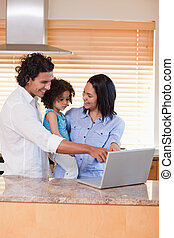 Family using notebook in the kitchen together - Young family...