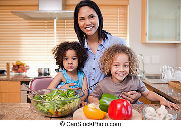 Young mother and her daughters preparing salad in the kitchen together