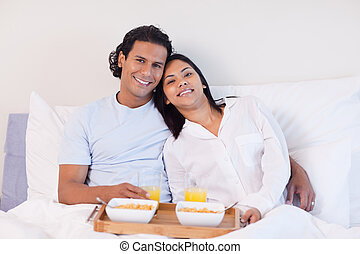 Couple enjoying breakfast in the bed - Young couple enjoying...