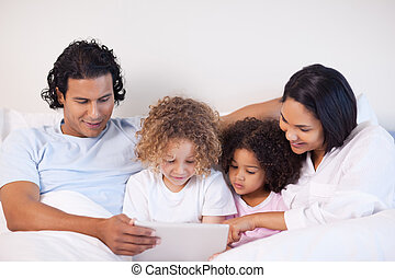 Family sitting on the bed surfing the web - Young family...