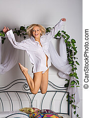 young woman jumping on the bed - sexy young woman jumping on...