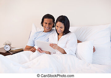 Couple surfing the internet on the bed - Young couple...