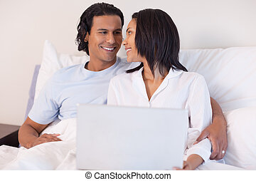 Young couple sitting on the bed with their laptop