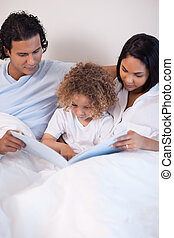 Family sitting on the bed reading a story