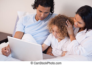 Family with laptop sitting on the bed