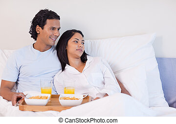 Couple having breakfast in the bed