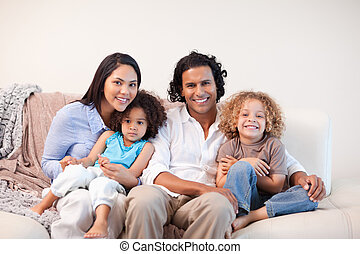 Cheerful family sitting on the sofa together