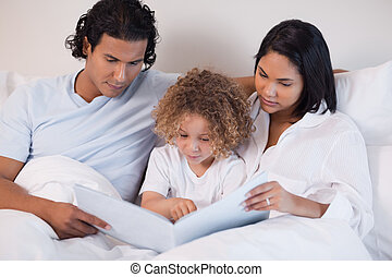 Happy family enjoys reading a book together