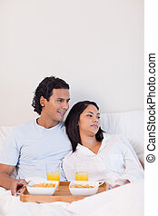 Couple eating breakfast in the bed