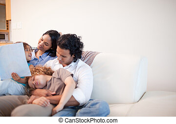 Family in the living room looking at photo album together