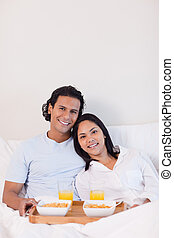 Happy couple having breakfast in the bed