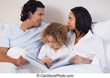 Family sitting on the bed reading a book