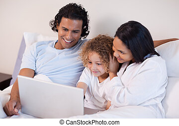 Family in the bedroom surfing the internet