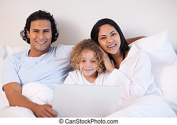 Family sitting on the bed with notebook