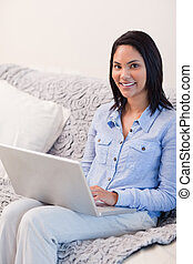 Woman in the living room surfing the internet