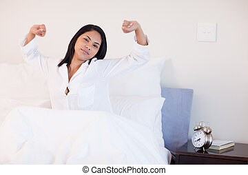Woman stretching to wake up - Young woman stretching to wake...
