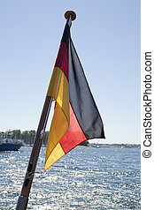German Flag Flying Over Ocean from a flagpole with coastline...