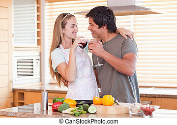 Lovely couple drinking wine in their kitchen