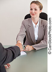 Portrait of a young manager shaking the hand of a customer