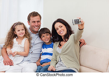 Mother taking family photograph on the couch