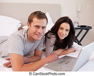Happy couple using laptop on the bed together - Happy young...