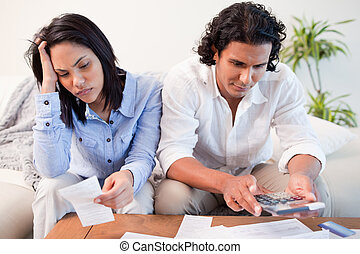 Couple having a hard time doing their finances - Young...