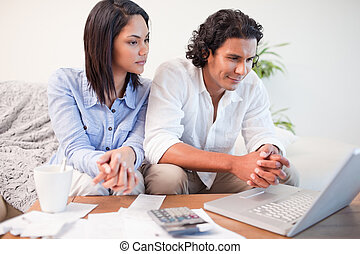 Couple sitting in the living room doing online banking -...